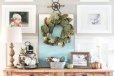 14 a farmhouse console with lots of pumpkins, baskets, pillows and a leaf wreath over it