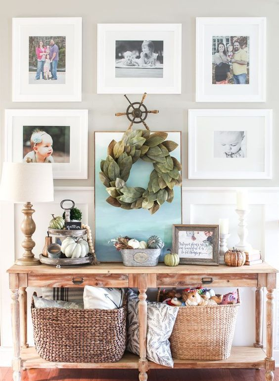 a farmhouse console with lots of pumpkins, baskets, pillows and a leaf wreath over it