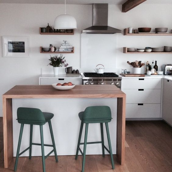 a minimalist waterfall kitchen island in white with a wooden countertop and colorful stools