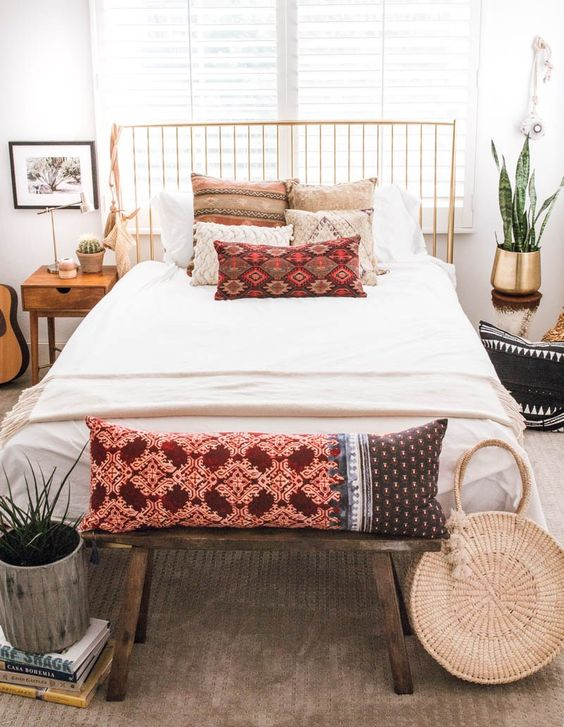 a straw round bag, bright printed pillows and fringed items for a boho chic space