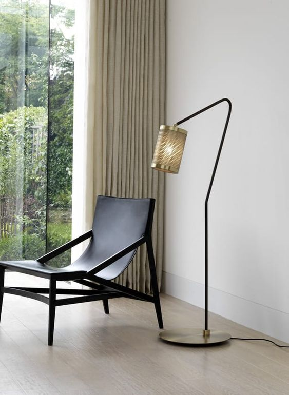 a stylish and refined floor lamp with a metal base and metal net lampshade adds style to the space