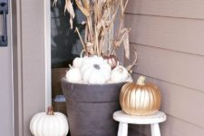 14 fall porch decor with white pumpkins, a gilded one, corn husks and a candle lantern