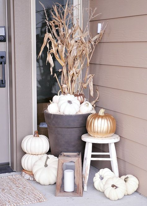 fall porch decor with white pumpkins, a gilded one, corn husks and a candle lantern