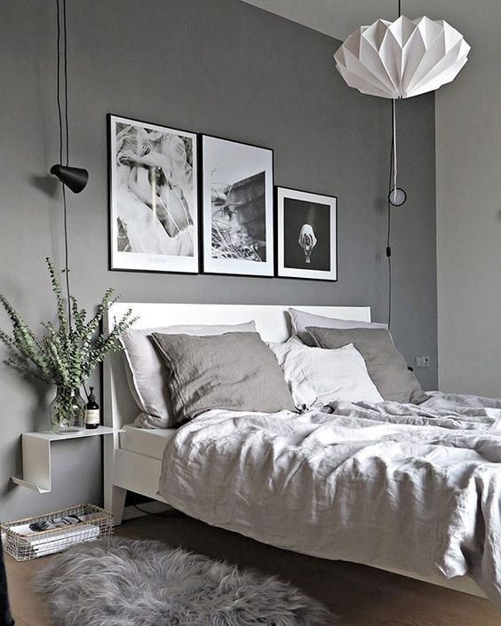a bedroom in various grey shades with a black and white gallery wall for a bold touch