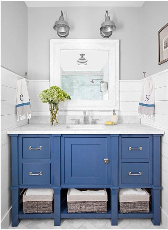 a blue vanity with baskets inside and a marble countertop for a coastal farmhouse bathroom