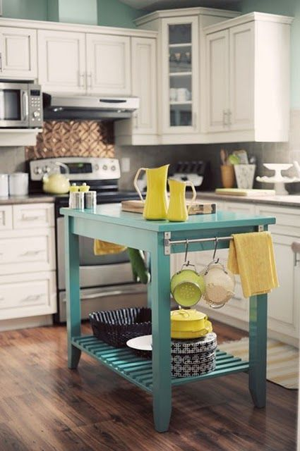 a bright turquoise kitchen island with a shelf and some holders adds color to the space