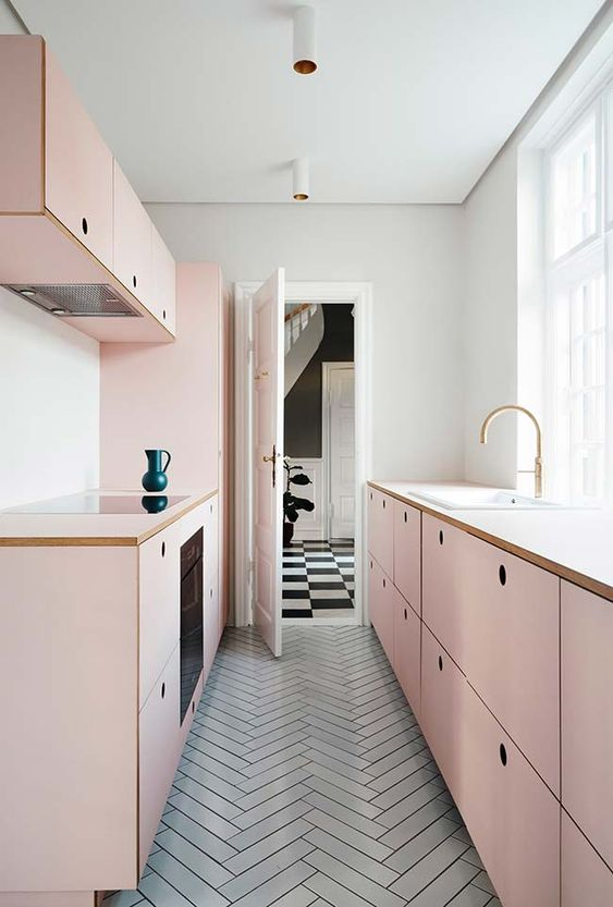 a chic girlish kitchen with simple blush cabinets and a grey tiled floor