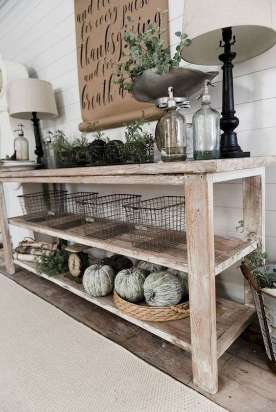 a farmhouse whitewashed console with green whitewashed pumpkins, greenery, wire baskets and lamps