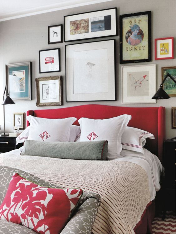 a grey bedroom spruced up with lots of artworks and a red upholstered bed