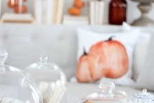 15 small faux pumpkins in a cloche is a simple and cool fall decoration for any space
