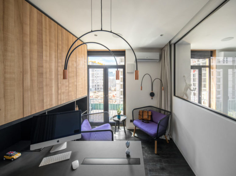 The home office shows off catchy purple chairs and unique arch hanging lamps