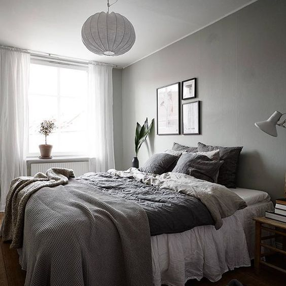a bedroom in various shades of grey spruced up with a small monochromatic gallery wall over the bed