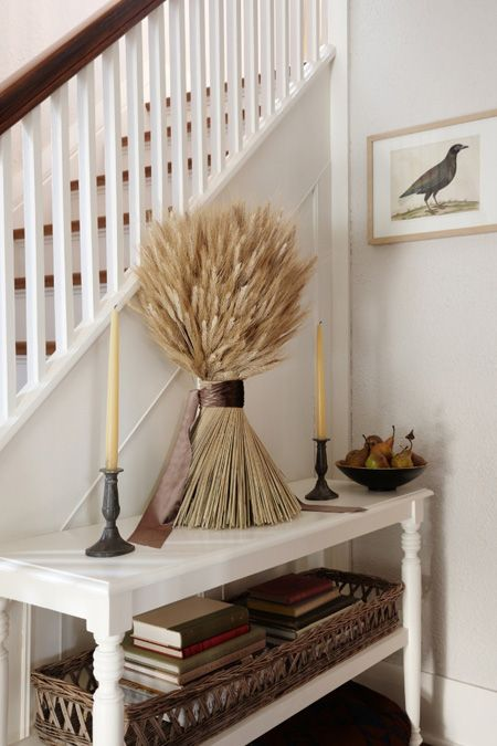 a fall console table with a pear bowl and a wheat bundle with a brown ribbon and candles