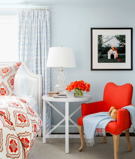 a hot red chair on wooden legs adds to the powder blue coastal bedroom