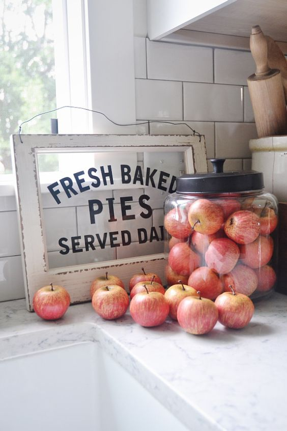a large jar with apples, faux or real ones, is a simple idea for a kitchen in the fall