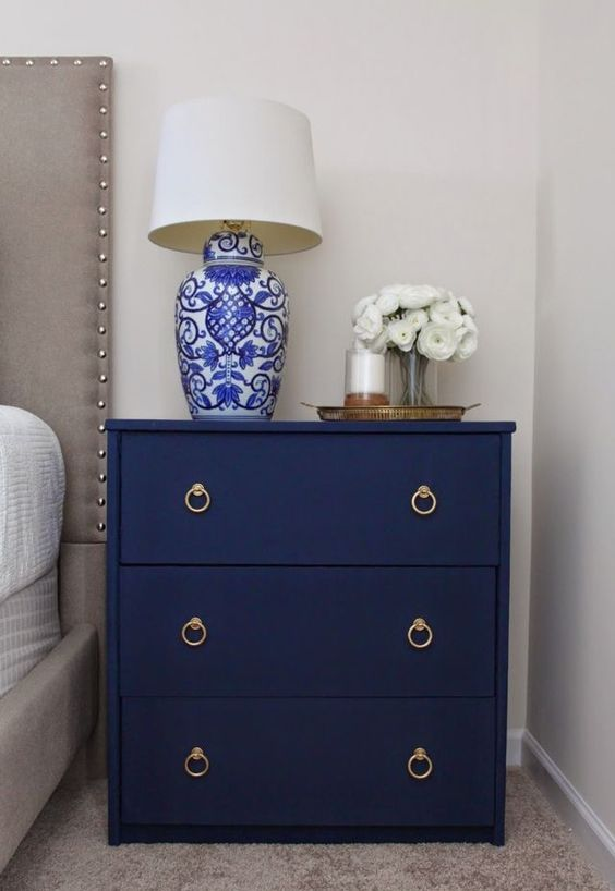 a navy fabric covered nightstand with elegant handles is a chic idea for any bedroom