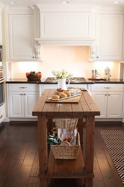 a rustic wood kitchen island contrasts white cabinets and features storage space underneath