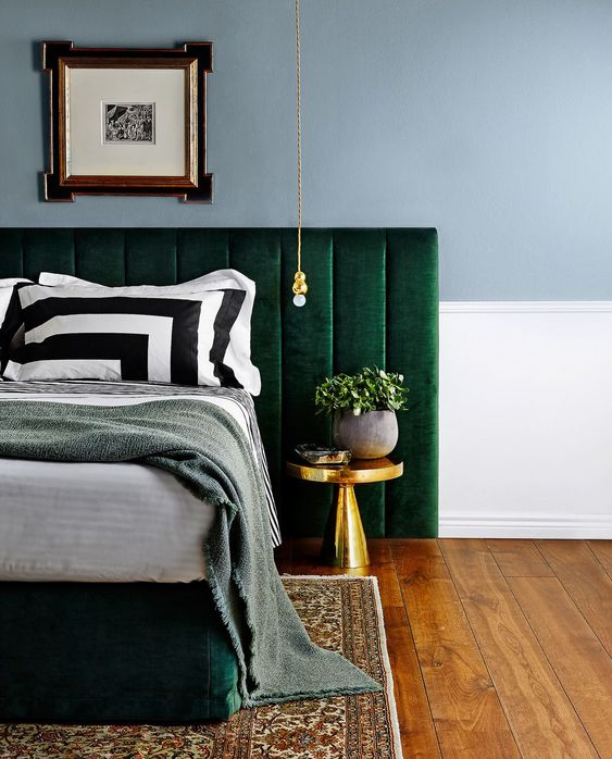 an upholstered emerald bed and a large headboard to add contrast and color to the space