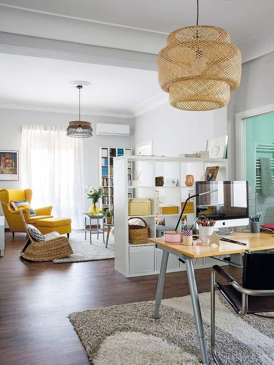 bright yellow touches in both spaces unite the open layout, which is still separated with a shelving unit