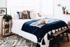 16 potted plants, bold boho pillows and a tassel bedspread are slight touches to make the space boho