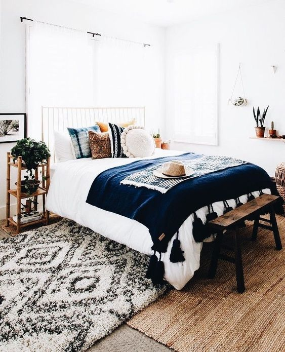 potted plants, bold boho pillows and a tassel bedspread are slight touches to make the space boho