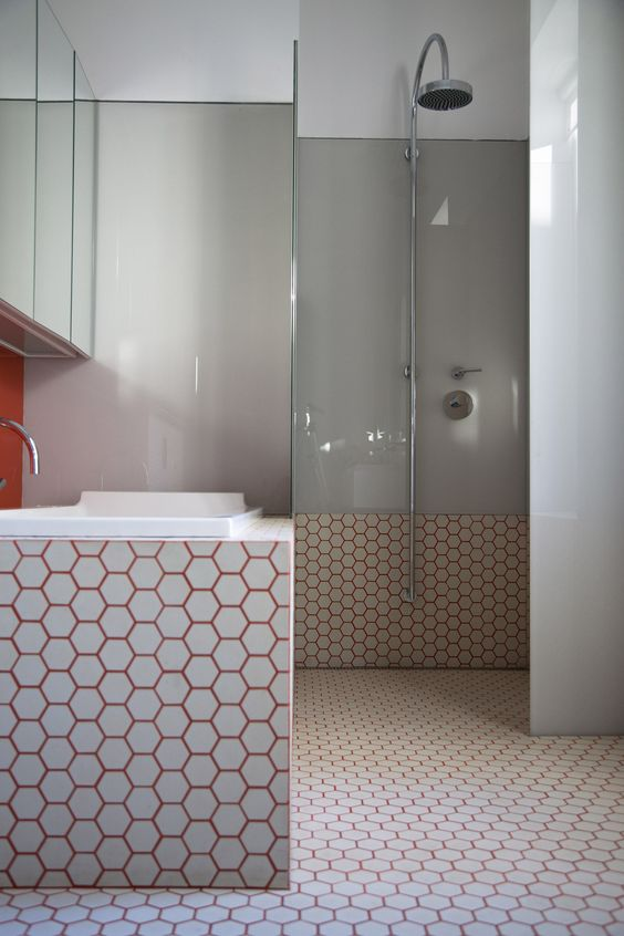 white hexagon tiles spruced up with burnt orange grout and paired with grey for a modern feel