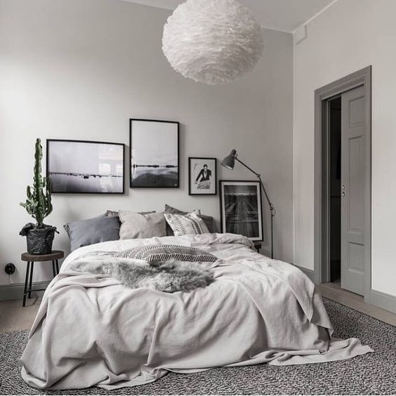 a chic gallery wall in black frames is what makes this grey bedroom eye-catchy