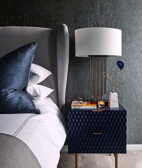 a cool textural navy nightstand adds an interesting touch to the space