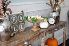 17 a fall console with orange and white pumpkins, fall leaves and dried blooms and firewood in a metal bathtub