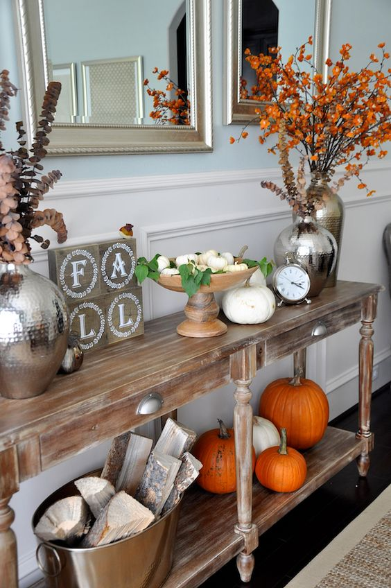 a fall console with orange and white pumpkins, fall leaves and dried blooms and firewood in a metal bathtub