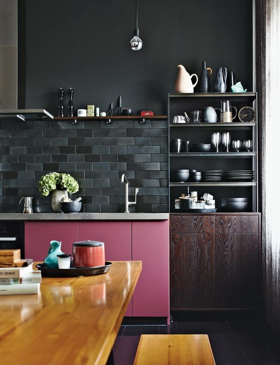 a moody kitchen in dark shades is spruced up with a bold pink cabinet and a bold stained table