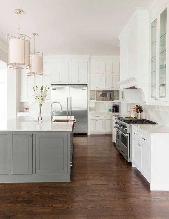 a traditional white kitchen with a grey kitchen island that adds a touch of color but not too much