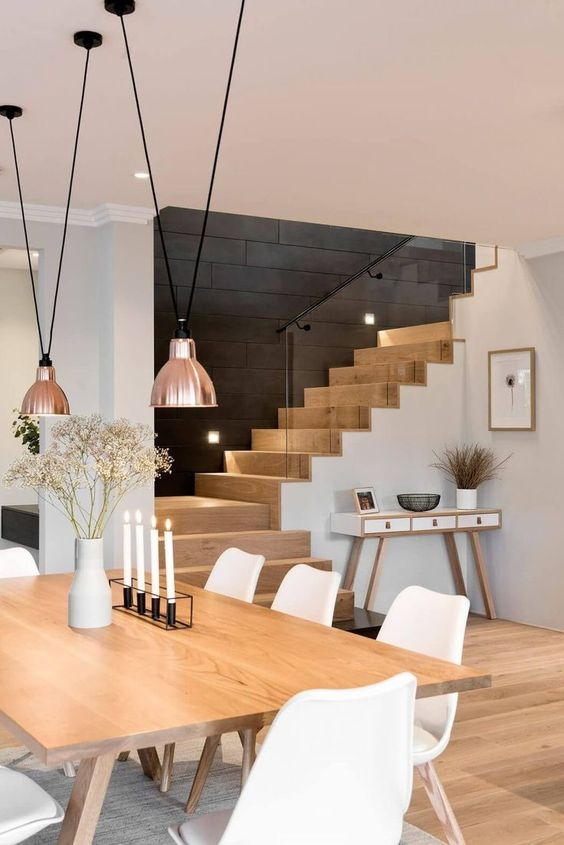 the dining room and entryway look as a cohesion and a ladder adds color to the space