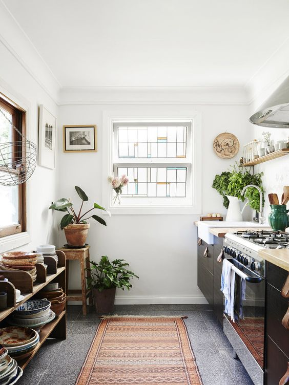 a boho chic kitchen with wooden touches and a boho rug plus potted greenery
