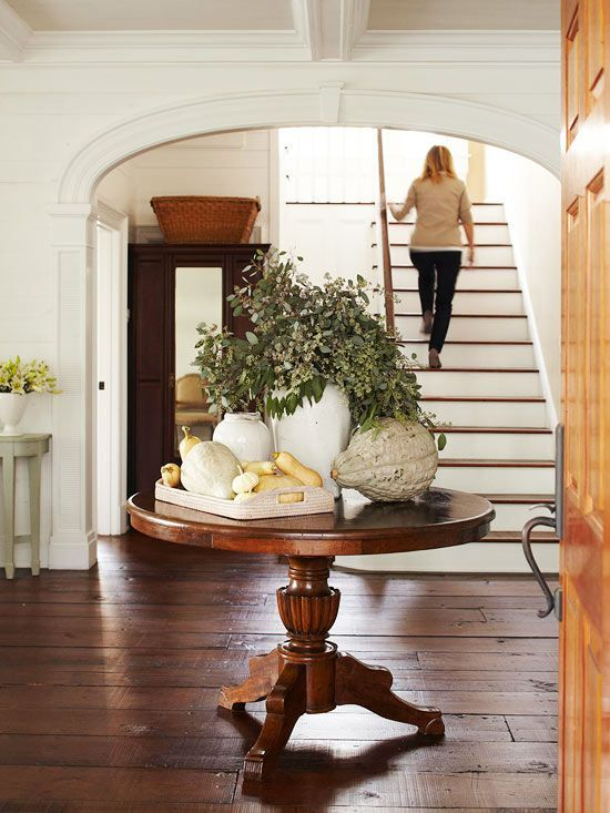 a farmhouse console table with real pumpkins and gourds and a greenery arrangement in a vase