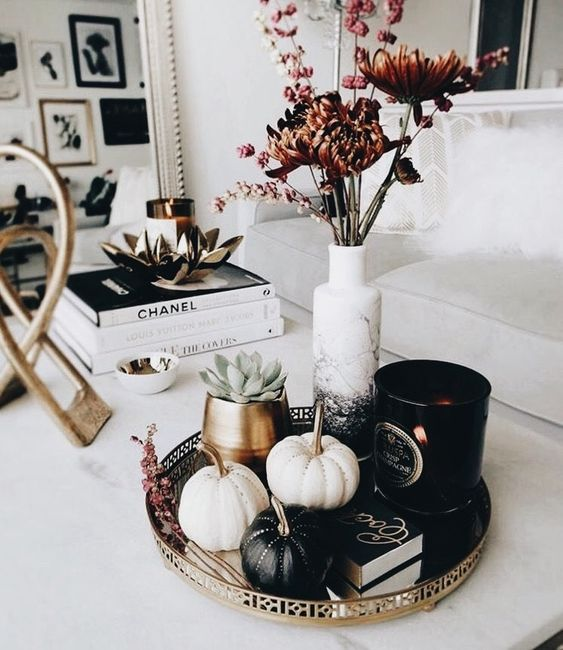 a stylish modern fall display with black and white pumpkins with rhinestones, succulents and dried blooms