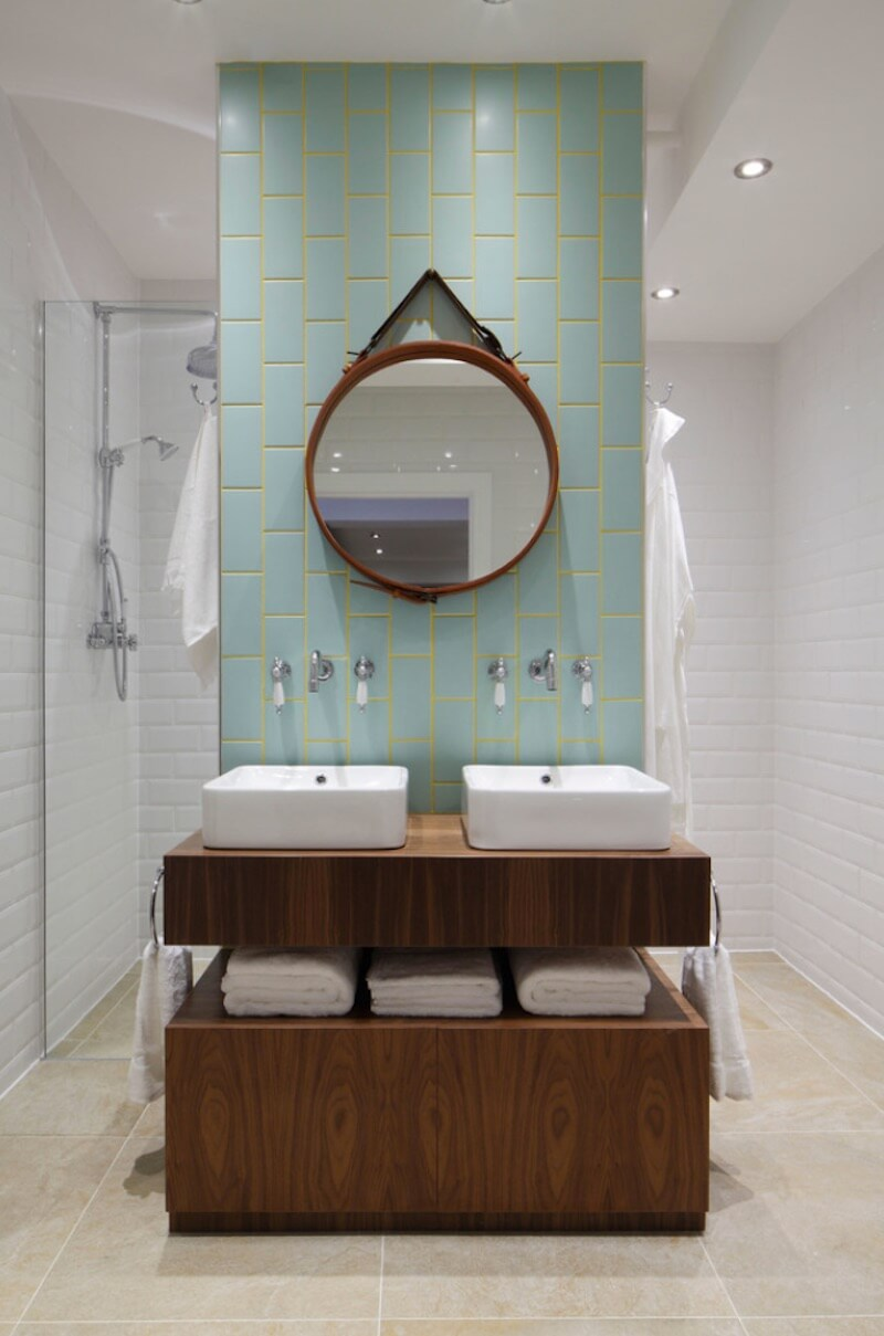 a vanity highlighted with blue tiles and neon yellow grout in between adds a colorful touch