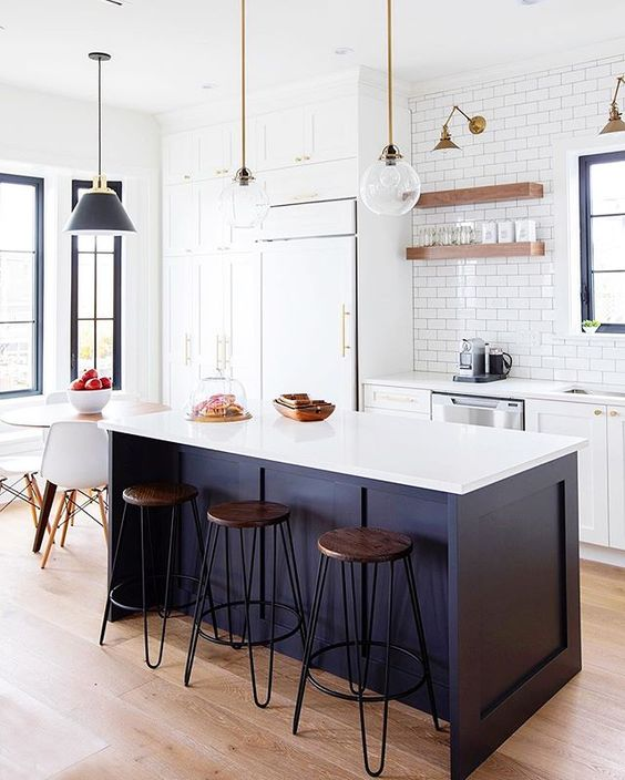 a white kitchen and a midnight blue kitchen island with a white countertop for a chic and catchy look