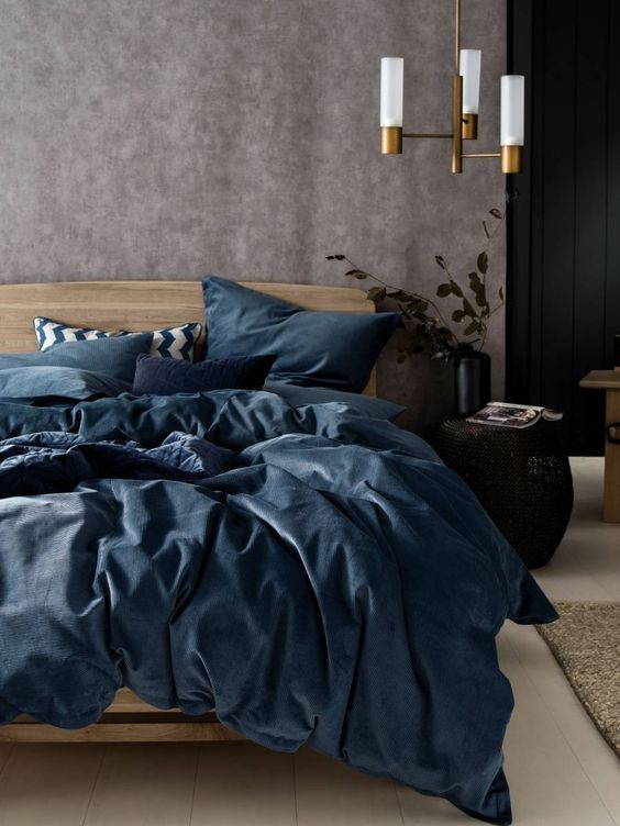 a bedding set in the muted shades of blue spruces up the space done in neutrals