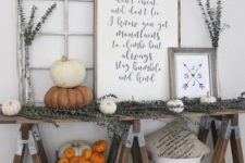 19 a farmhouse trestle table with dried eucalyptus, white and orange pumpkins, signs and baskets
