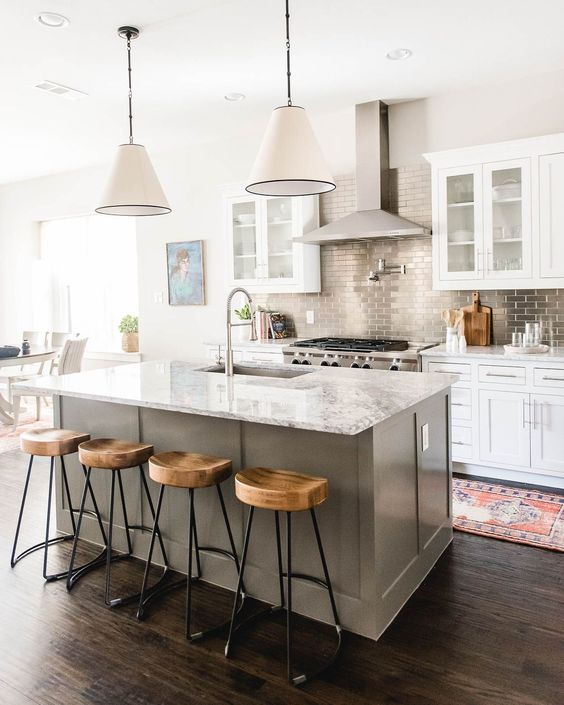 a white kitchen with a grey kitchen island, a stone countertop and a metallic tile backsplash add interest