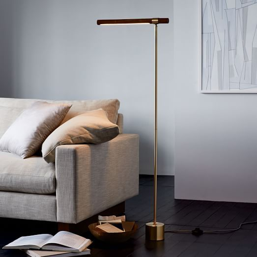 an elegant minimalist floor lamp with a thin metal leg, a metal base and a wooden linear lampshade