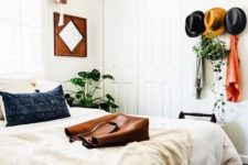 19 give a boho feelto your bedroom with some hats on the wall, potted greenery and boho bedding