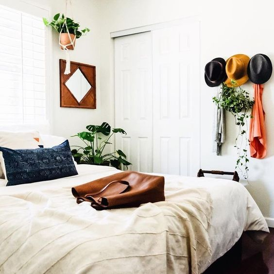 give a boho feelto your bedroom with some hats on the wall, potted greenery and boho bedding