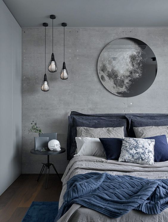 a chic grey and navy bedding set plus a blue rug enliven the grey bedroom