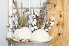 20 a farmhouse display with white pumpkins, wheat and cotton in a metal bathtub