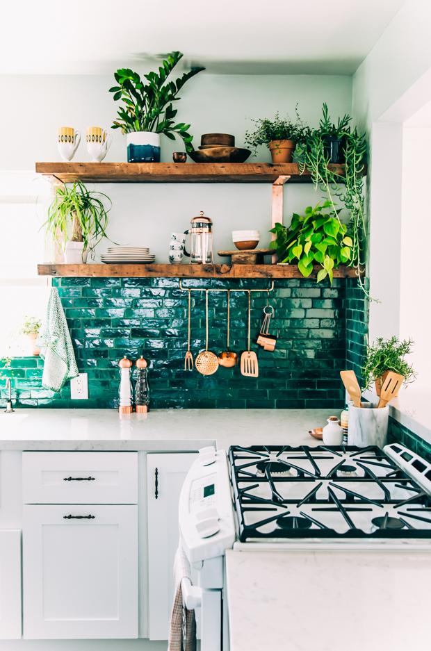 a gorgeous emerald tile backsplash and wooden shelves make up a stunning setup for a boho kitchen