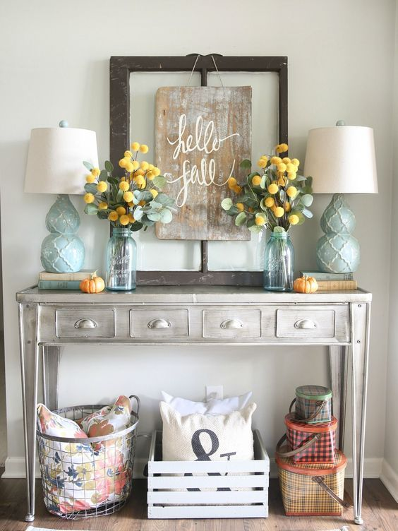a grey console table with aqua lamps, a worn wooden sign and eucalyptus and craspedia arrangements