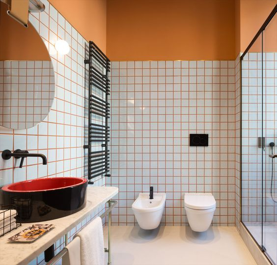spruce up your bathroom with colorful grout like here with orange grout and orange half walls
