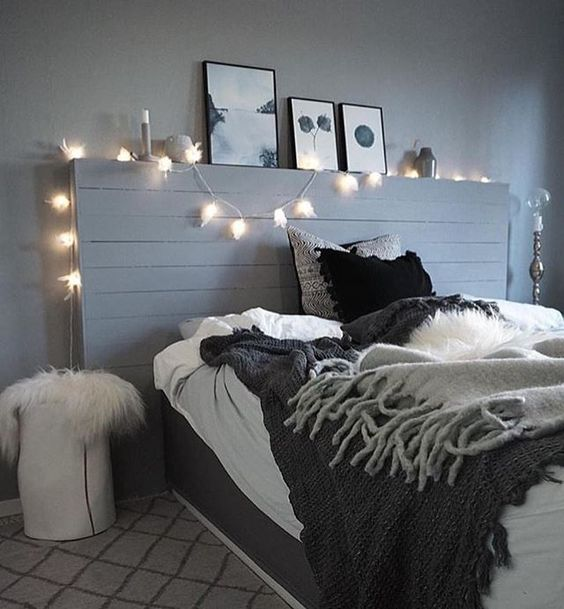 a grey bedroom spruced up with lights and a monochromatic gallery wall, black bedding